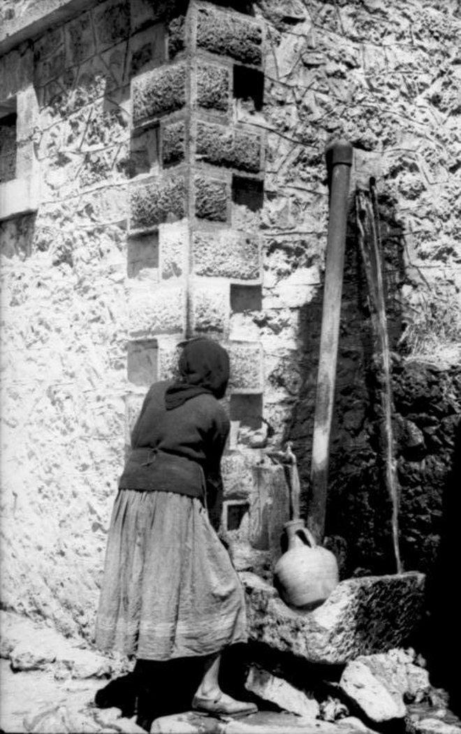 Ο Γερμανός φωτογραφίζει μια κρητικοπούλα, σε βρύση του χωριού.