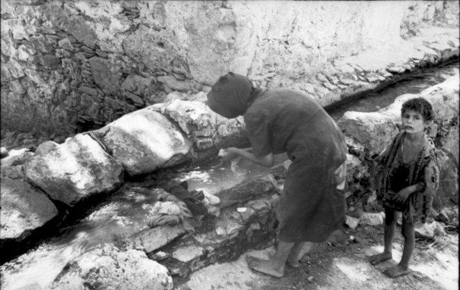 Με περιέργεια, ο πιτσιρίκος κοιτάζει τον φωτογράφο ενώ η μητέρα του πλένει. Σε λίγες εβδομάδες, οι φωτογραφικές μηχανές αντικαταστάθηκαν από τα όπλα...